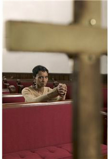 woman praying on pew before a cross